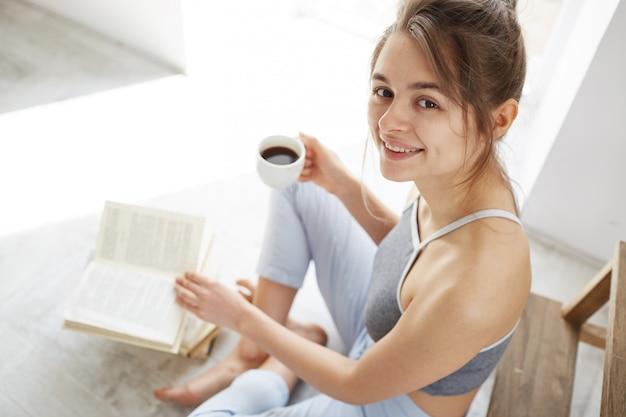 Portrait de la belle femme heureuse souriant tenant une tasse de café assis sur le sol avec un livre.