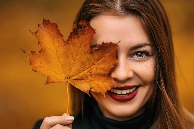 Portrait d'une belle femme heureuse avec un sourire avec une feuille jaune d'automne dans le parc