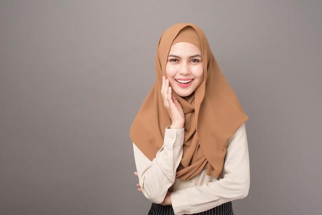 Portrait de la belle femme avec hijab sourit sur mur gris