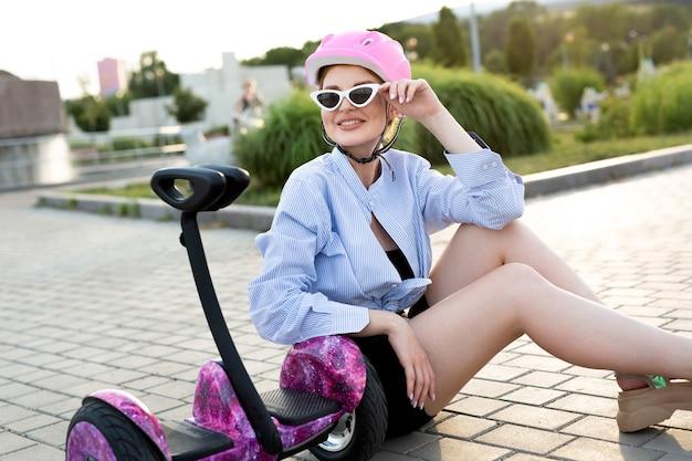 Portrait d'une belle femme sur un hoverboard ou un scooter gyroscopique dans le parc