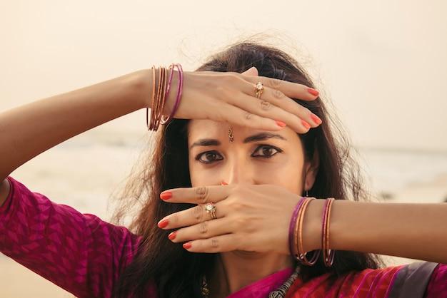 Portrait de la belle femme indienne en sari rouge dansant