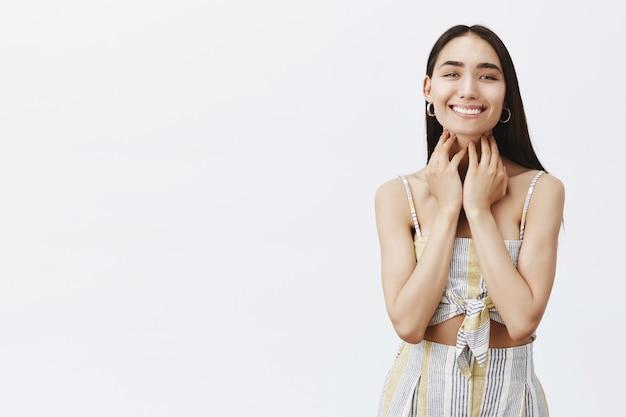 Portrait de la belle femme insouciante et joyeuse souriant largement après avoir vu les résultats de la procédure cosmétologique, en prenant soin de la peau sur un mur gris
