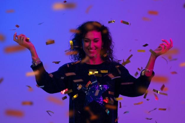 Portrait de belle femme jouant avec des confettis. célébration, anniversaire, noël, nouvel an.