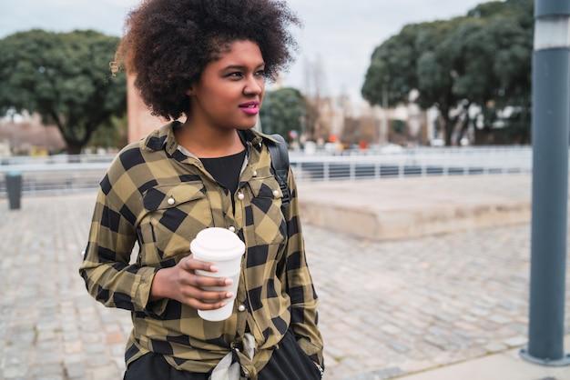 Portrait de la belle femme latine afro-américaine tenant une tasse de café à l'extérieur dans la rue. concept urbain.