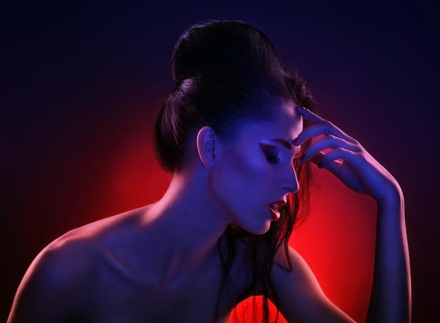 Portrait de belle femme en lumière rouge et bleue