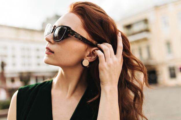 Portrait de la belle femme à lunettes de soleil à l'extérieur
