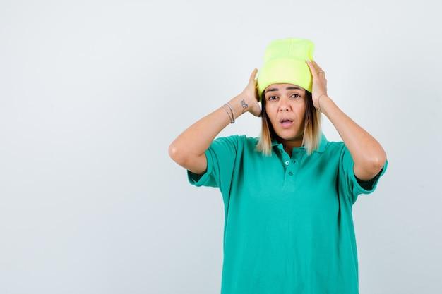 Portrait de belle femme avec les mains sur la tête en t-shirt polo, bonnet et à la vue de face perplexe