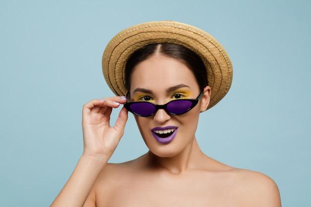 Portrait de belle femme avec maquillage lumineux, chapeau et lunettes de soleil sur fond bleu studio. marque et coiffure élégantes et à la mode. couleurs de l'été. beauté, concept publicitaire. regarde des lunettes.