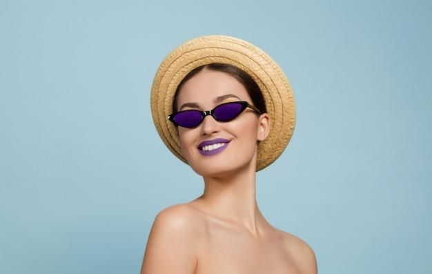 Portrait de belle femme avec maquillage lumineux, chapeau et lunettes de soleil sur fond bleu studio. marque et coiffure élégantes et à la mode. couleurs de l'été. beauté, mode, concept publicitaire. regarde de côté.