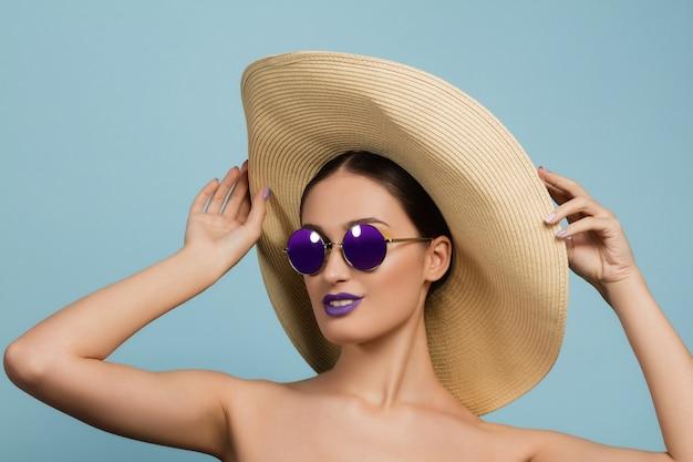 Portrait de belle femme avec maquillage lumineux, chapeau et lunettes de soleil. marque et coiffure élégantes et à la mode.