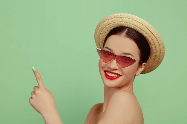 Portrait de belle femme avec maquillage lumineux, lunettes rouges et chapeau. marque et coiffure élégantes et à la mode. couleurs de l'été. montrer du doigt.