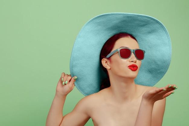 Portrait de belle femme avec maquillage lumineux, lunettes rouges et chapeau sur studio vert