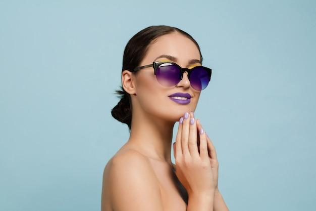Portrait de belle femme avec maquillage lumineux et lunettes de soleil. marque et coiffure élégantes et à la mode. couleurs de l'été. sérieux, confiant.