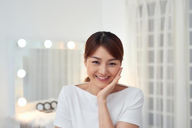 Portrait d'une belle femme avec un maquillage naturel touchant son visage. jeune femme de beauté avec une peau parfaite propre et fraîche.