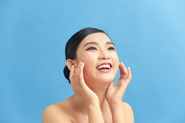 Portrait d'une belle femme avec un maquillage naturel touchant son visage.