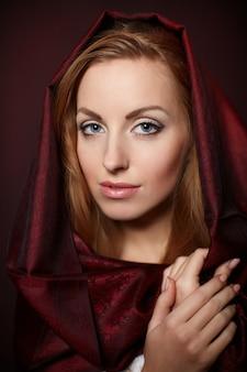 Portrait, de, belle femme, à, maquillage soirée., modèle, poser, dans, studio, à, textile rouge, sur, elle, tête