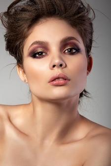 Portrait de la belle femme avec le maquillage des yeux charbonneux rouge et or romantique