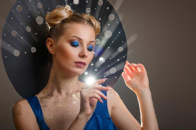 Portrait d'une belle femme maquillée, chapeau original rayons de lumière