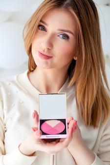 Portrait belle femme maquilleuse tenir correctif sculptant palette rose blush avec miroir.