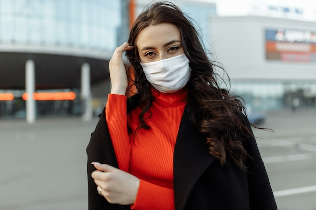 Portrait de belle femme marchant dans la rue portant un masque de protection comme protection contre les maladies infectieuses. modèle malheureux attrayant avec la grippe à l'extérieur.