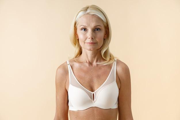 Portrait de belle femme mature aux cheveux blonds en sous-vêtements blancs regardant la caméra debout