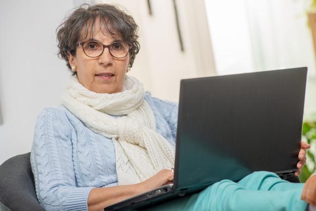 Portrait de belle femme mature brune avec un ordinateur portable à la maison