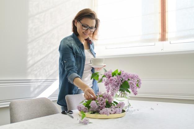 Portrait de belle femme mature à la maison avec bouquet de lilas