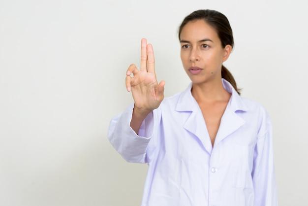 Portrait de la belle femme médecin multiethnique touchant quelque chose
