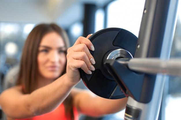 Portrait de la belle femme met la plaque de poids sur la barre dans la salle de gym