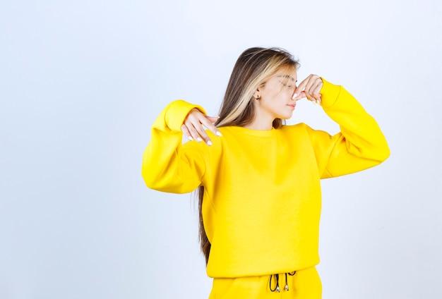 Portrait de belle femme modèle debout et posant en t-shirt jaune