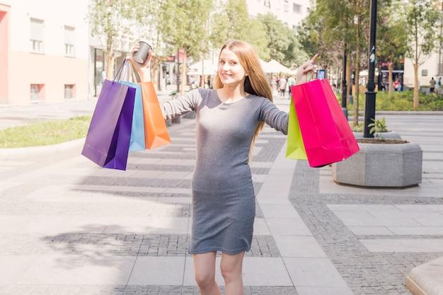 Portrait d'une belle femme montrant des sacs à provisions multicolores