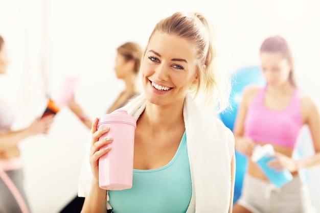 Portrait de belle femme mûre avec la bouteille souriante dans le club de santé