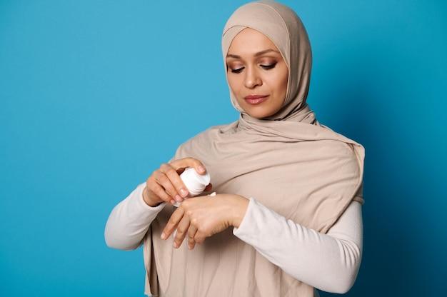 Portrait de la belle femme musulmane arabe en hijab pressant la crème sur place, isolé