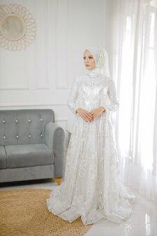 Portrait de la belle femme musulmane vêtue d'une robe de mariée blanche