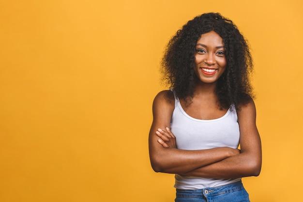 Portrait de la belle femme noire afro-américaine positive debout avec les bras croisés
