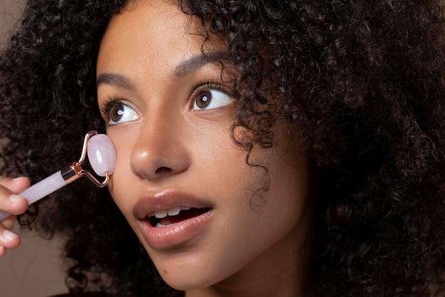 Portrait de belle femme noire à l'aide d'un rouleau de jade sur son visage