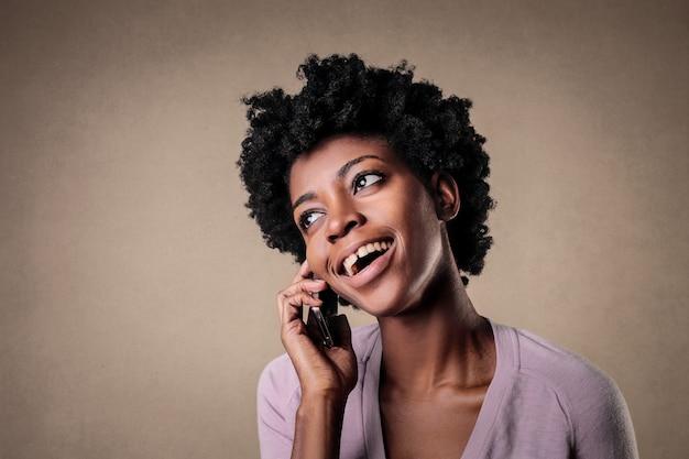 Portrait d'une belle femme noire parlant joyeusement sur son cellohine