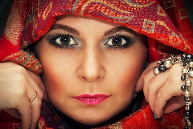 Portrait d'une belle femme orientale dans un foulard traditionnel, gros plan.