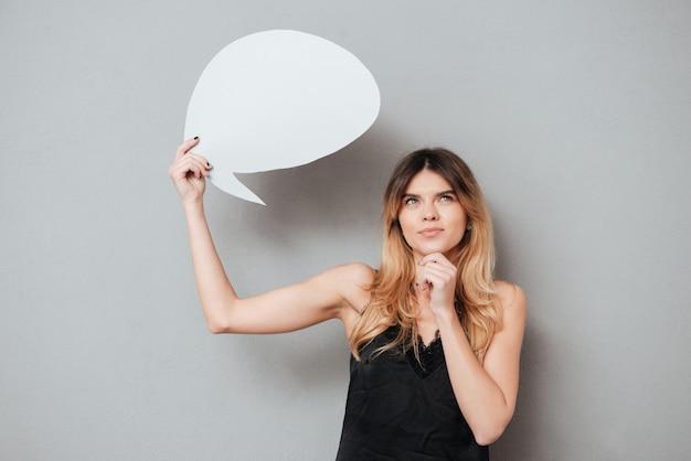 Portrait d'une belle femme pensive tenant la bulle de dialogue