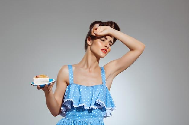 Portrait de la belle femme pin up refusant de manger du gâteau