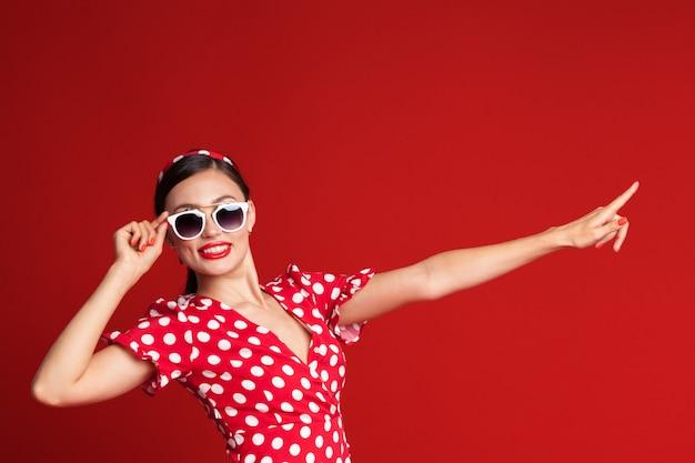 Portrait d'une belle femme pin-up style rétro pointant