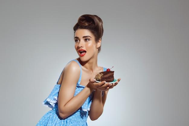 Portrait de la belle femme pin-up tenant le gâteau dans les mains