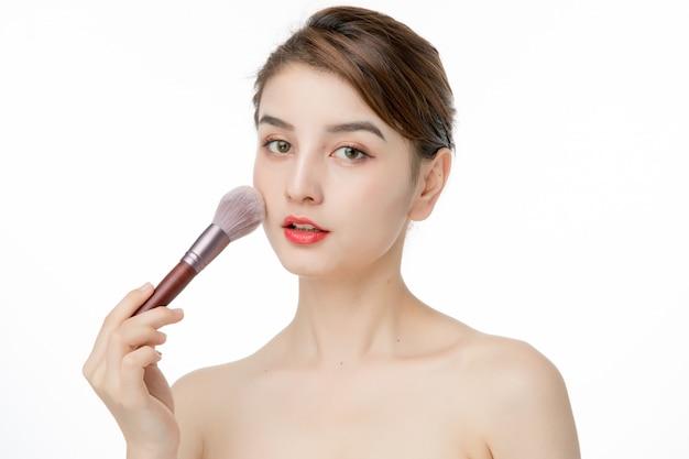Portrait de la belle femme pin up tenant le pinceau de maquillage