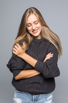 Portrait d'une belle femme portant un pull en tricot chaud sur son corps sur un fond gris isolé