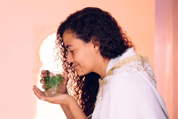 Portrait de la belle femme portant une robe blanche ethnique et buvant du thé arabe