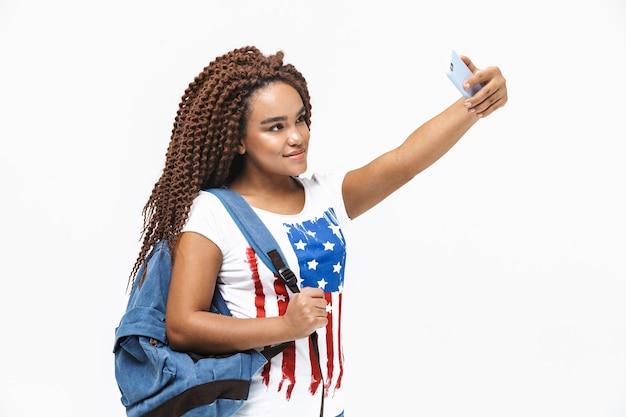 Portrait d'une belle femme portant un sac à dos souriant et prenant une photo de selfie sur un téléphone portable tout en se tenant isolé contre un mur blanc