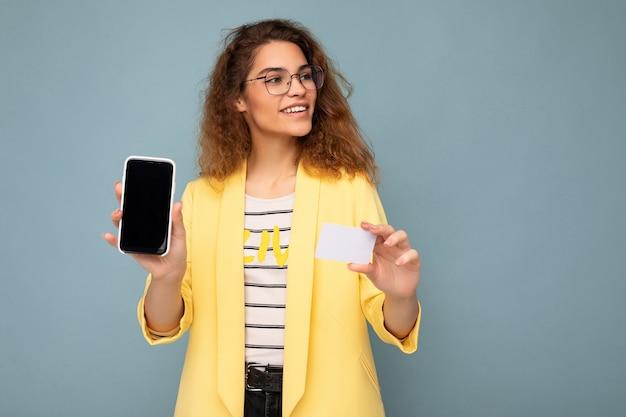 Portrait d'une belle femme portant une veste jaune et des lunettes optiques isolées sur un mur de fond tenant et montrant un téléphone avec un écran vide et une carte de crédit regardant sur le côté