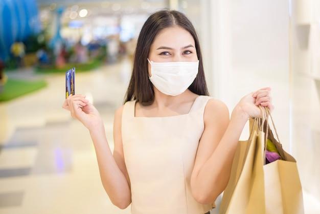 Portrait de la belle femme porte un masque facial dans le centre commercial