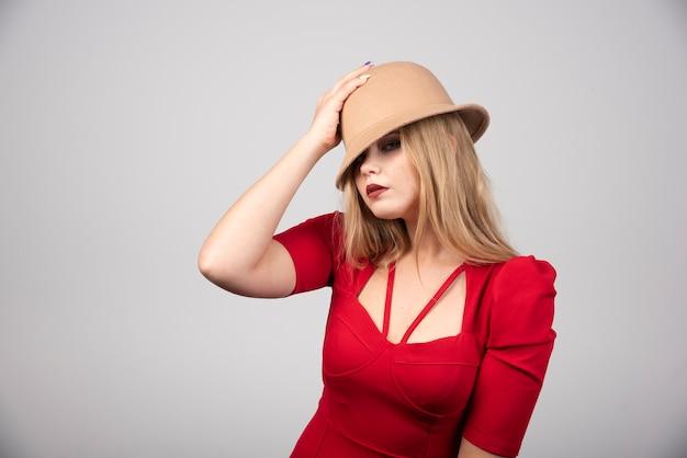 Portrait de belle femme posant avec chapeau.
