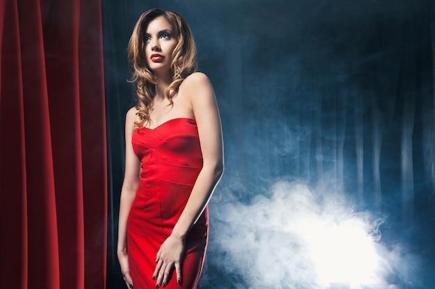 Portrait d'une belle femme posant dans une robe rouge devant les scènes
